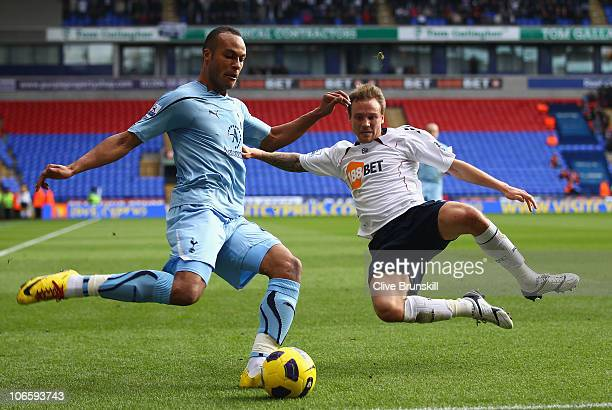 Younes Kaboul of Tottenham Hotspur attempts to cross the ball past Matt Taylor of Bolton Wanderers during the Barclays Premier League match between...