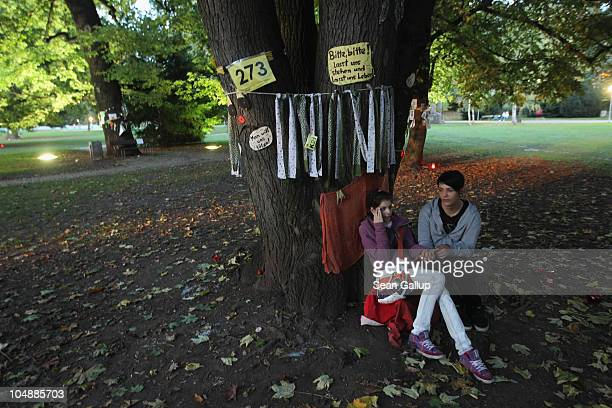 A younf couple sit at one of the nearly 300 trees slated for removal in the Schlosspark next to Hauptbahnhof train station on October 6 2010 in...