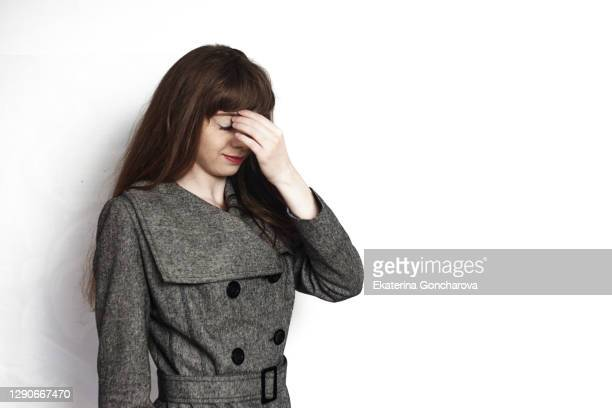 a young 20 year old girl stands on a white isolated background in a jacket and smiles - dekubitus stock-fotos und bilder