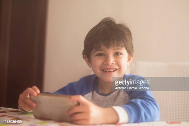 young 4 years old kid looking phone at home and looking at camera smiling - 4 5 years stock pictures, royalty-free photos & images