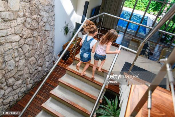 young 6 and 8 year old sisters climbing stairs at home - moving up stock pictures, royalty-free photos & images