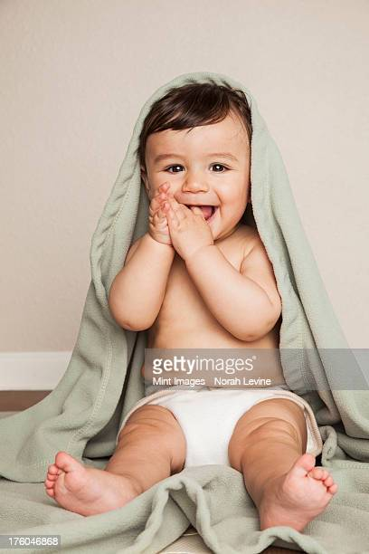 A young 8 month old baby boy wearing cloth diapers, sitting on the floor. A cot blanket over his head.