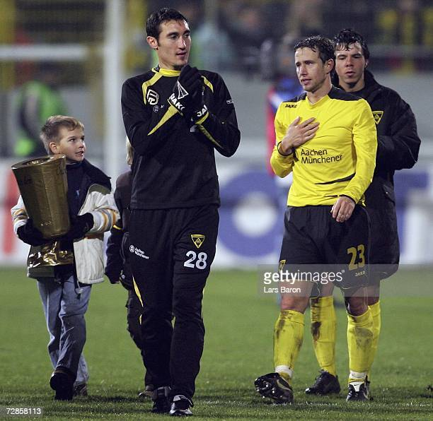 A young Aachen fan caries a cup replica next to Laurentiu Reghecampf of Aachen after the DFB German Cup third round match between Alemannia Aachen...