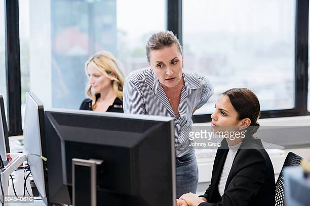 Young Aboriginal Australian woman in office with business colleague