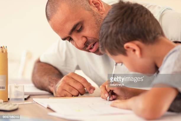 young aboriginal boy doing homework with the help of his father. - aboriginal australian ethnicity stock pictures, royalty-free photos & images