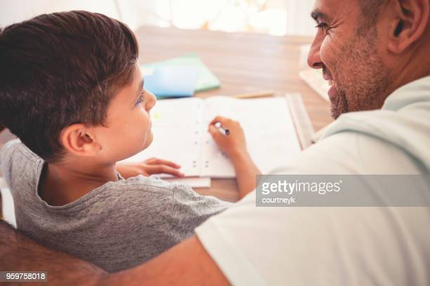 Young Aboriginal boy doing homework with the help of his father.