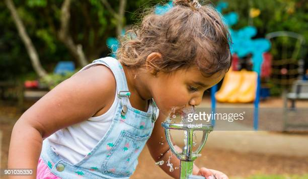 young aboriginal girl drinking from a water fountain - drinking water stock pictures, royalty-free photos & images