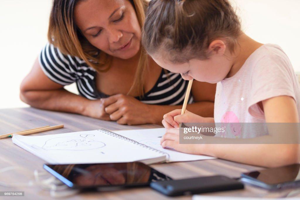 Aboriginal jungen Mädchen studieren mit der Mutter zu helfen. : Stock-Foto