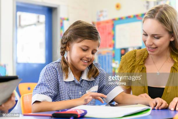 Young Aboriginal girl using digital tablet with her teacher helping