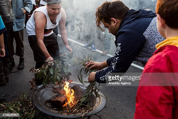 Young Aboriginal men look on as they burn Gum leaves during a rally protesting against the forced closure of Aboriginal Communities in Australia on...