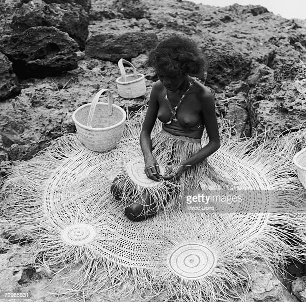 A young Aborigine woman weaves grass into a circular mat in Arnhem Land in the Northern Territory of Australia circa 1950