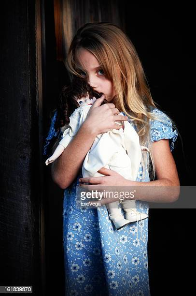 Young abused girl with her doll