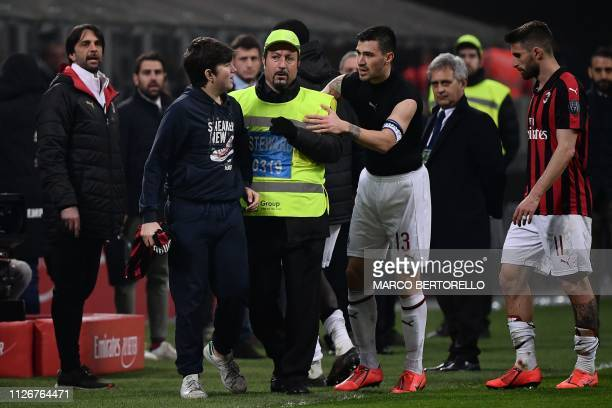 A young AC Milan supporter holds the jersey given by AC Milan's Italian defender Alessio Romagnoli at the end the Italian Serie A football match AC...