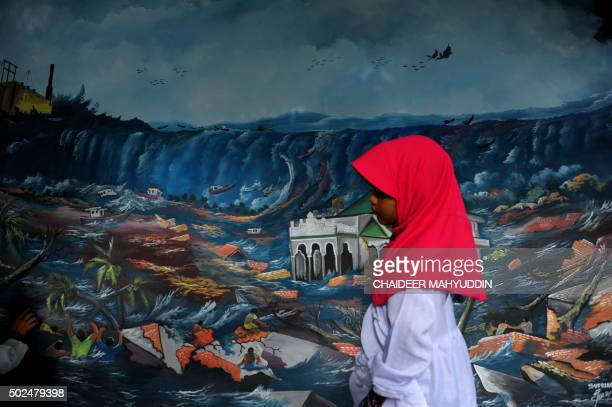 A young Acehnese girl walks past a tsunami mural at the Ulhee Lheue mass cemetary where thousands of the 2004 tsunami victims are buried in Banda...