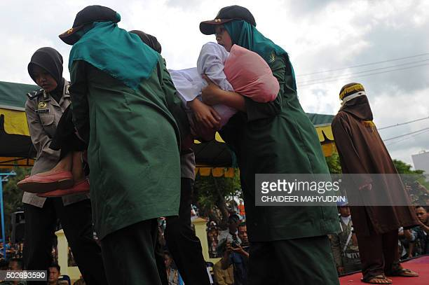 A young Acehnese woman is carried by officials after being caned in public a punishment under the Islamic sharia law under the offence of khalwat or...
