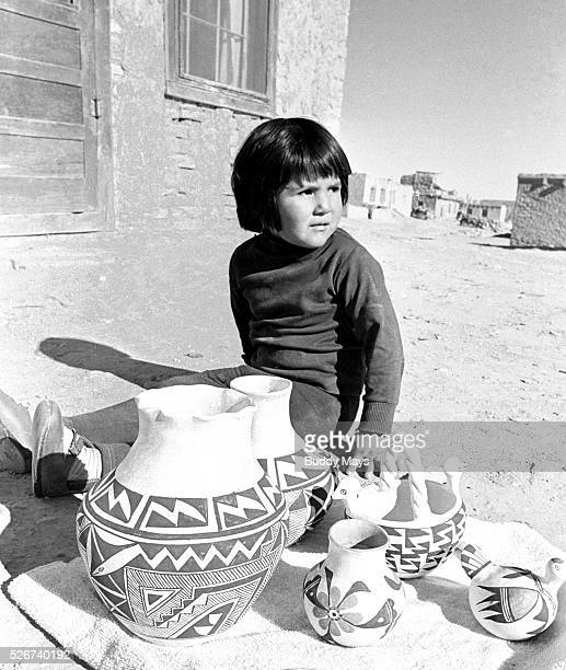 NEW MEXICO A young Acoma Indian girl sits on the ground at Acoma Pueblo selling her mother's traditional clay pottery Acoma sits atop a steep mesa...