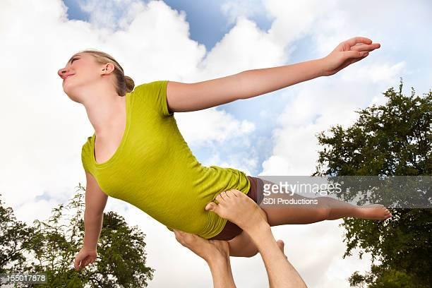 Giovane acrobata in equilibrio sul piede facendo Acroyoga