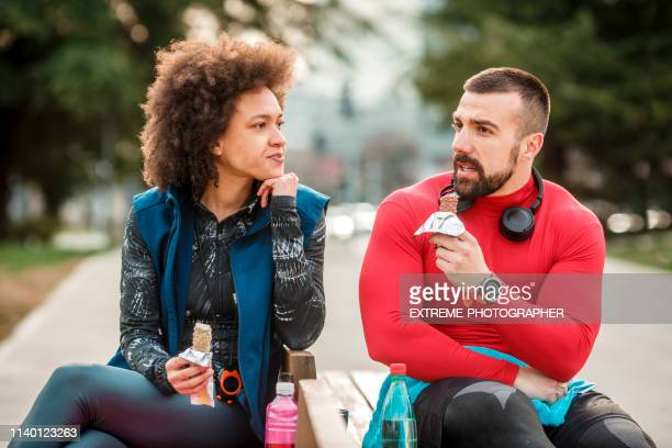 young active man eating a protein bar with his partner while sitting on a bench in a city park, having a discussion - candy wrapper stock photos and pictures