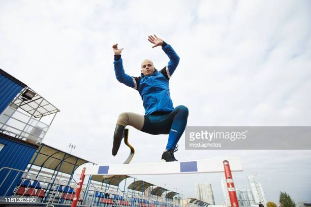 young active runner with prosthetic curved blade jumping over obstacles while hurdling at stadium - pessoas com deficiência imagens e fotografias de stock