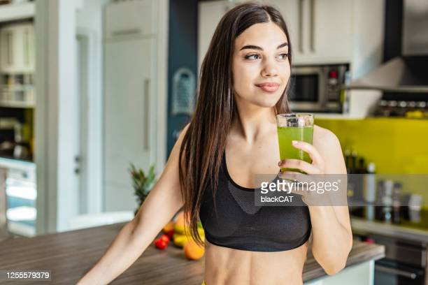 young active woman holding healthy smoothie - juice drink stock pictures, royalty-free photos & images