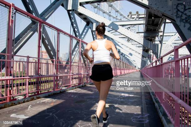 young active woman running on williamsburg bridge - forward athlete stock pictures, royalty-free photos & images