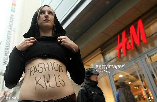 A young activist from the labor rights group verdi shows her stomach with the words 'Fashion Kills' written on it during a demonstration in the rain...