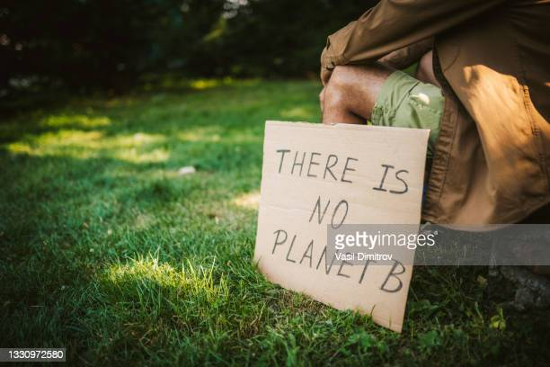 young activist / protester. environmental conservation / climate change protest. - striker stock pictures, royalty-free photos & images