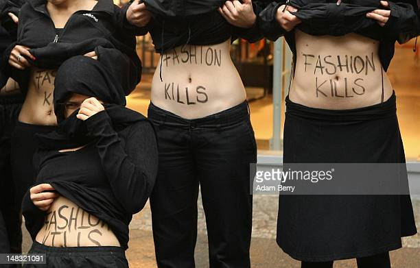 Young activists from the labor rights group verdi show their stomachs with the words Fashion Kills written on them during a demonstration in the rain...