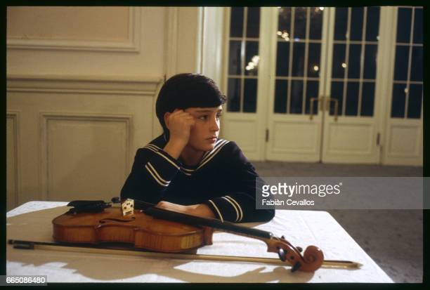 Young actor David Eberts sits with a violin on the set of the 1988 movie Burning Secret or Brennendes Geheimnis in German Directed by British...