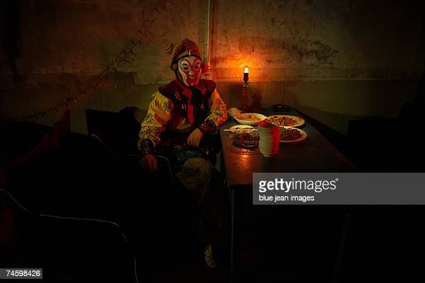 young actor dressed as a traditional beijing opera comedian sits down at a table in front of several dishes of food. - beijing opera stock photos and pictures
