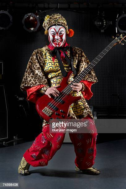 young actor dressed as monkey king poses on stage with an electric bass. - masked musicians stock-fotos und bilder