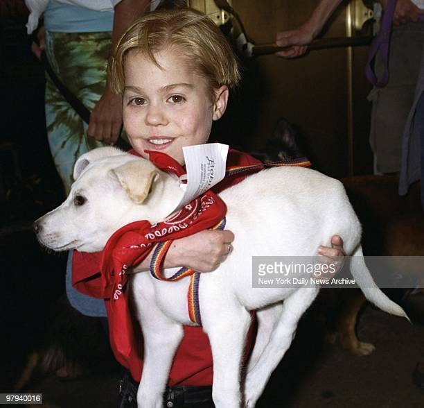 Young actor Josh Ryan Evans hoists a pooch which is up for adoption during the Broadway Barks 3 benefit at Shubert Alley The annual event encourages...