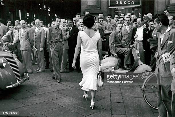 Young actress and circus performer Moira Orfei walks towards the Galleria Vittorio Emanuele II in Milan Italy while a large group of men turn to look...
