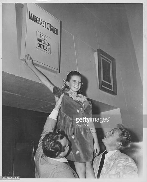Young actress Margaret O'Brien held up by actors Red Skelton and Van Johnson unveiling a bronze plaque dedicated to her in the 'Hall of Fame'...