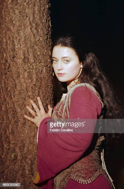 Young actress Monica Keena playing Lilliana Hoffman and wearing an aristocrat's dress poses with her hands around a tree at night time on the set of...