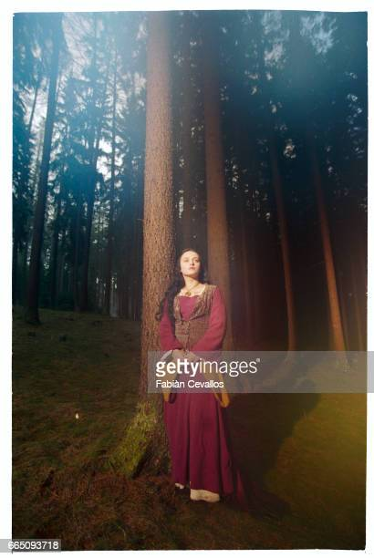 Young actress Monica Keena stands in the middle of a forest with high trees behind her on the set of the movie Snow White A Tale of Terror Directed...
