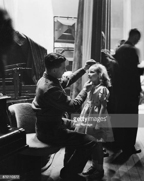Young actress Petula Clark gets a last-minute check from her father, Lance Corporal Leslie Clark, before going on stage at the BBC's Empire birthday...