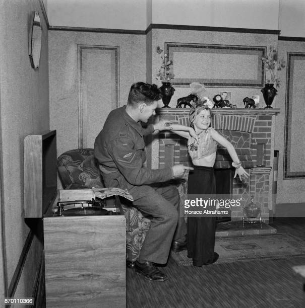 Young actress Petula Clark rehearses her impression of Carmen Miranda in front of her father, Lance Corporal Leslie Clark, at their home in...