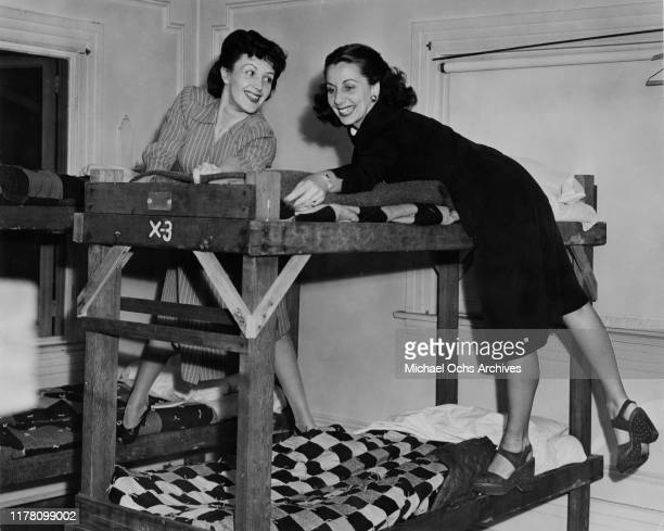Young actresses Kay Linaker and Mickie Kelly make beds for GIs in the dormitory of the Hollywood Canteen in Los Angeles California during World War...