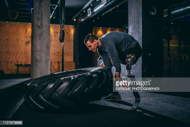 Young adaptive sportsman doing a tire flip gym exercise in a gym