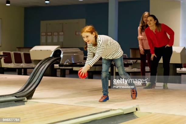 Young adult and preteen girls playing bowling.
