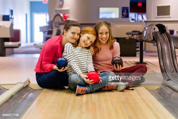 Young adult and preteen girls posing in bowling alley.