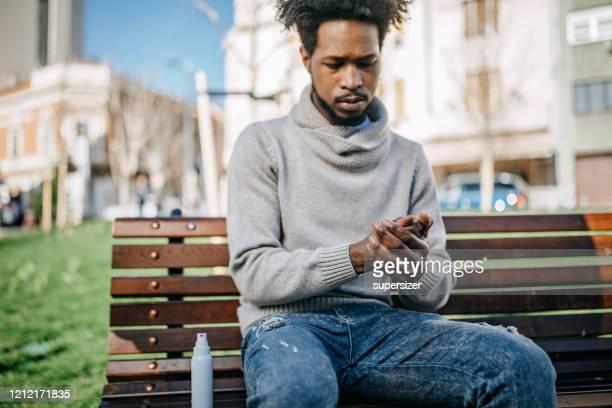 jonge volwassene die handlotion toepast - handcrème stockfoto's en -beelden