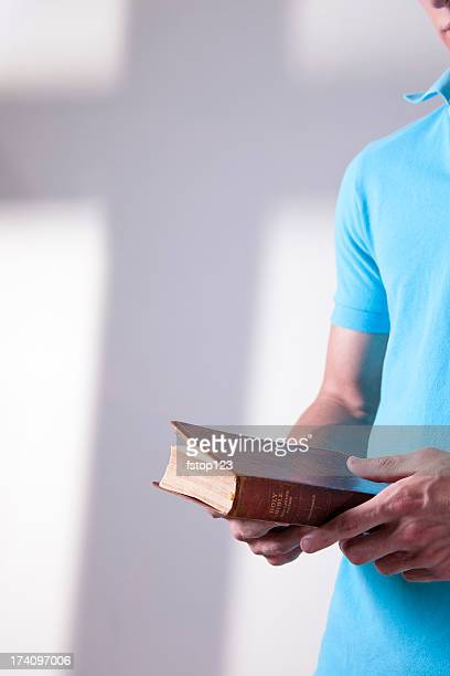 Young adult Bible in hands cross shadow on wall