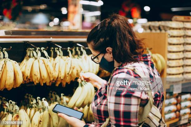 young adult brazilian woman shopping for bananas in face mask with smart phone - helena price stock-fotos und bilder