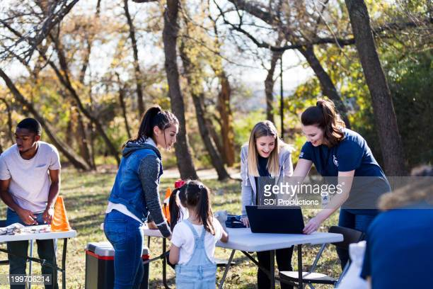 young adult brings little sister to volunteer at park cleanup - non profit organization stock pictures, royalty-free photos & images