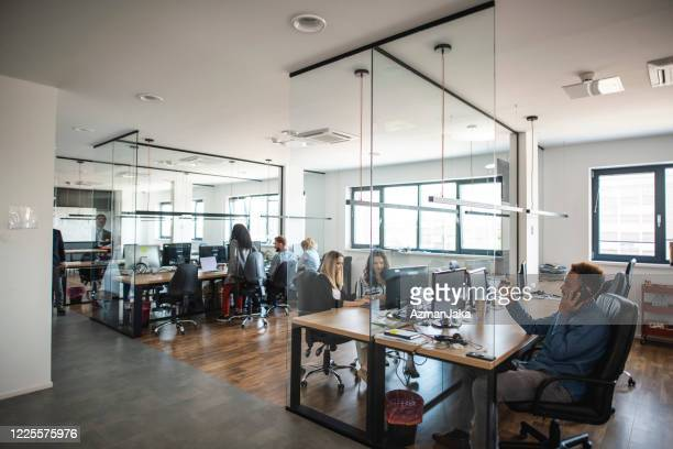 young adult business colleagues working in open plan office - open plan stock pictures, royalty-free photos & images