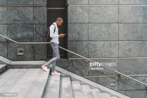 giovane uomo d'affari adulto in città scendendo le scale con lo smartphone - walking foto e immagini stock