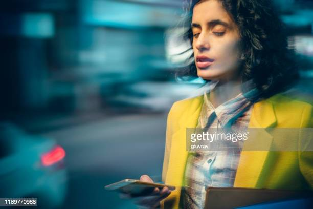 young adult businesswoman after heavy use of smartphone feels dizzy at night on a busy road. - differential focus stock pictures, royalty-free photos & images