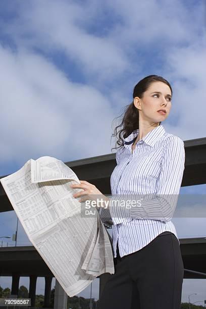 a young adult businesswoman holding a newspaper, three quarter length, low angle view - three quarter length ストックフォトと画像
